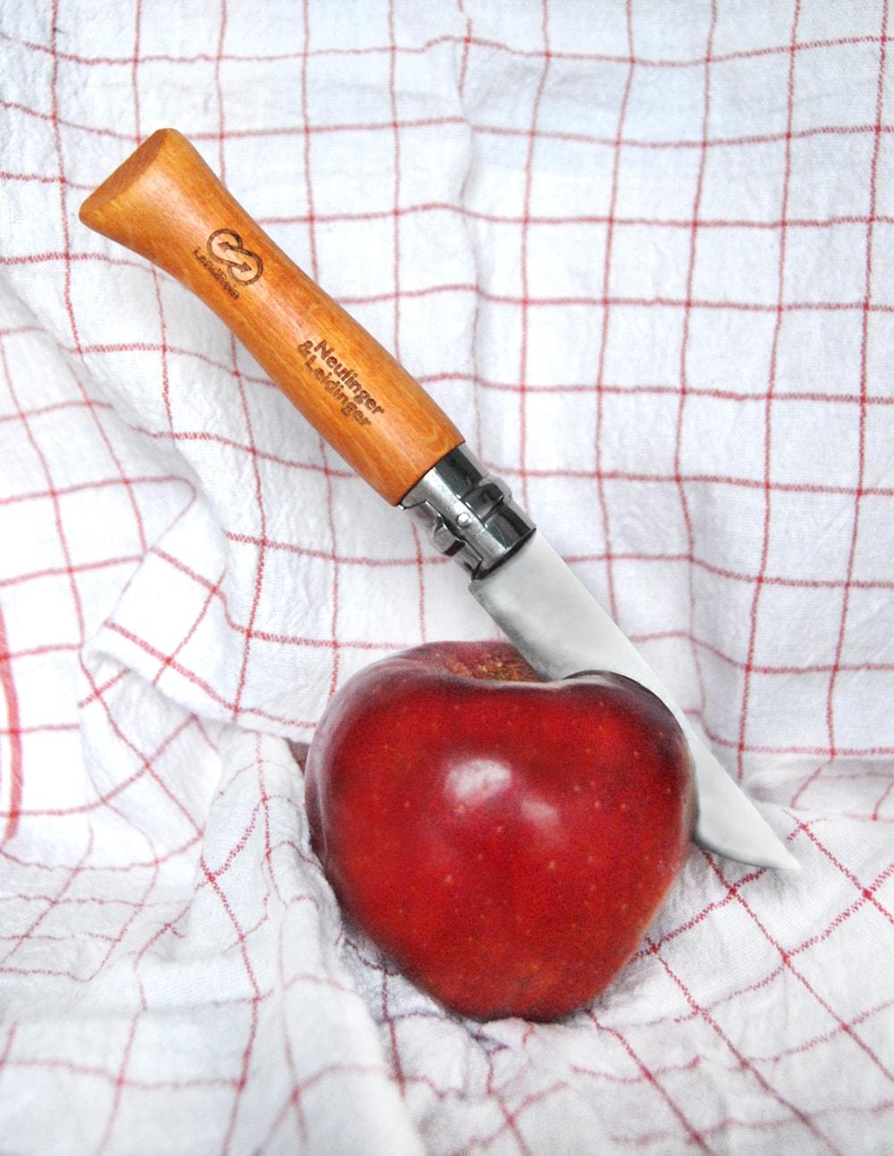 Messer mit gelasertem Holzgriff steckt in Apfel